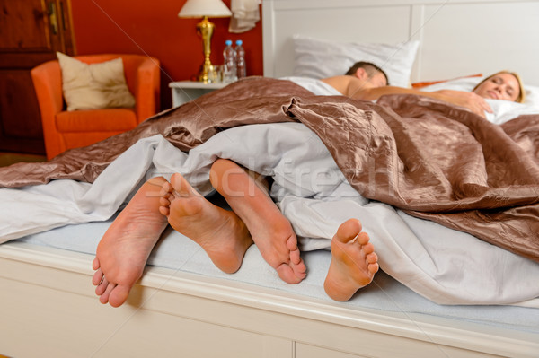 Lovers foot poking out bed covers sleeping Stock photo © CandyboxPhoto