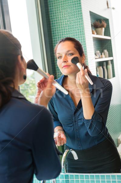Stock photo: Young woman applying face powder bathroom brush
