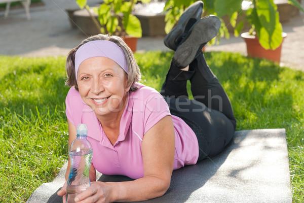 Senior sportive woman lying on mat sunny Stock photo © CandyboxPhoto