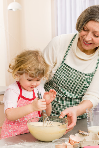 Grandmother and granddaughter whisk dough Stock photo © CandyboxPhoto