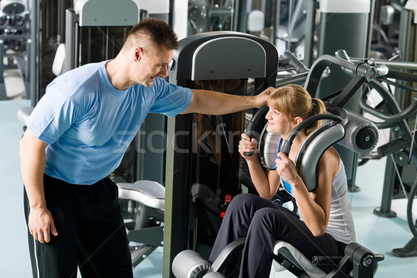 Fitness center young woman exercise with trainer Stock photo © CandyboxPhoto