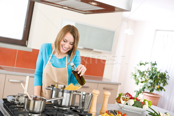 Stock photo: Cooking - Young woman with spaghetti on stove