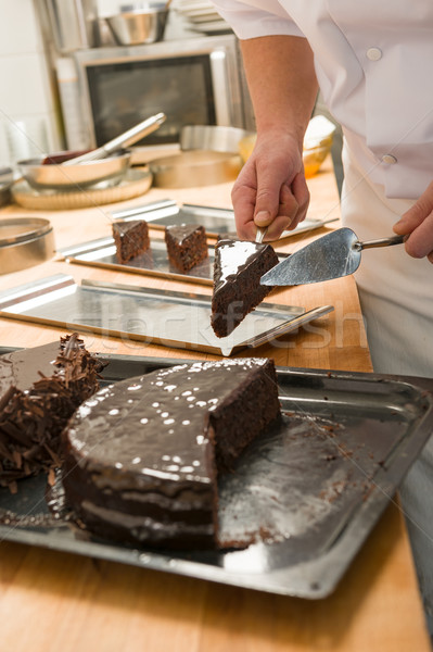 Confectioner cutting a slice of chocolate cake Stock photo © CandyboxPhoto