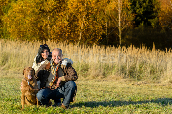 Cheerful couple with dog in autumn countryside Stock photo © CandyboxPhoto