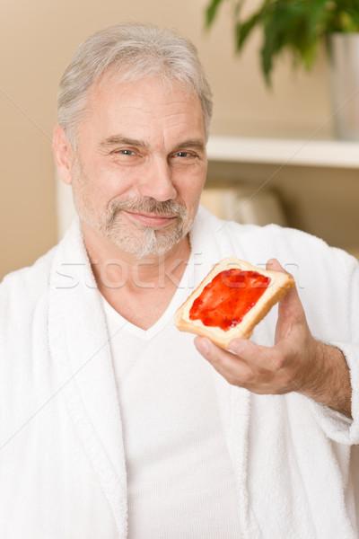 Senior homem maduro café da manhã casa comer pão Foto stock © CandyboxPhoto