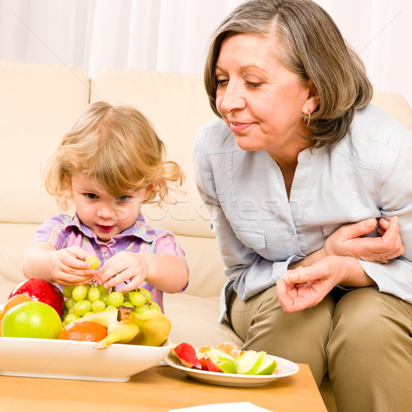 Grandmother with granddaughter eat fruit at home Stock photo © CandyboxPhoto