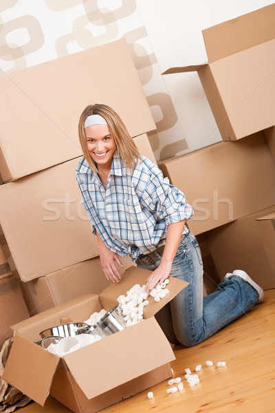 Moving house: Happy woman unpacking box Stock photo © CandyboxPhoto