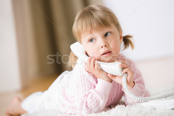 Little girl lying down on carpet with phone calling Stock photo © CandyboxPhoto