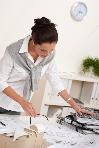 Stock photo: Smiling female architect working with plans