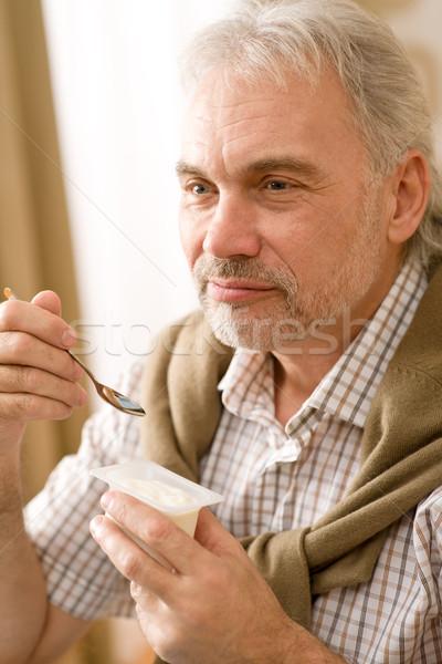 Idős érett férfi eszik joghurt falatozó tart Stock fotó © CandyboxPhoto