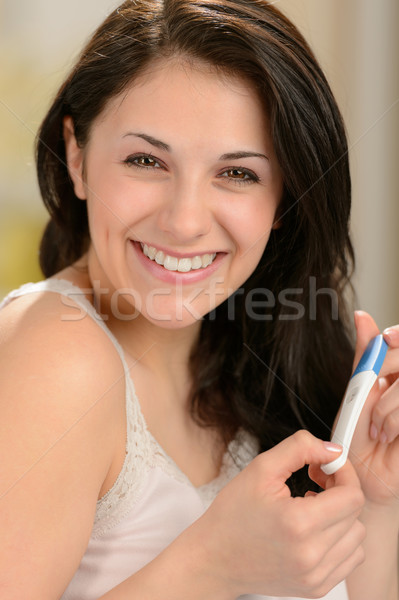 Cheerful young woman holding pregnancy test Stock photo © CandyboxPhoto
