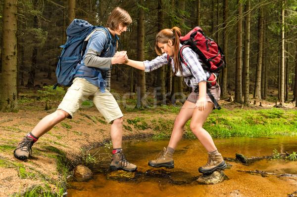 Hiker boy help trekking girl crossing creek Stock photo © CandyboxPhoto