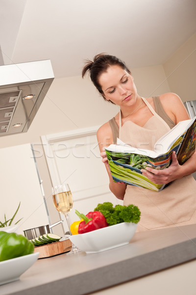 Young woman reading cookbook in the kitchen Stock photo © CandyboxPhoto