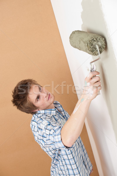 Stock photo: Home improvement: Young man with paint roller