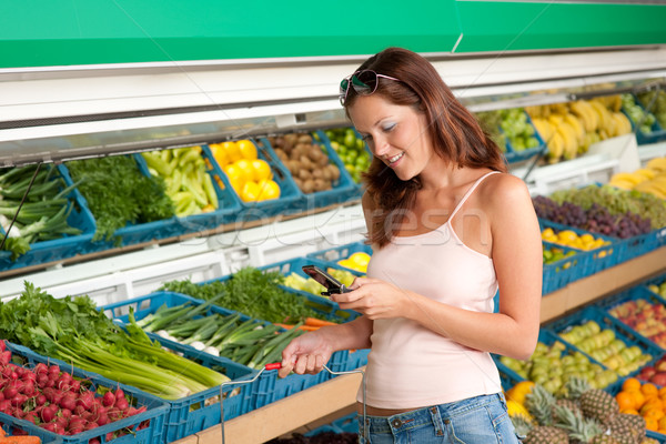 Stock photo: Grocery store shopping - Woman holding mobile phone
