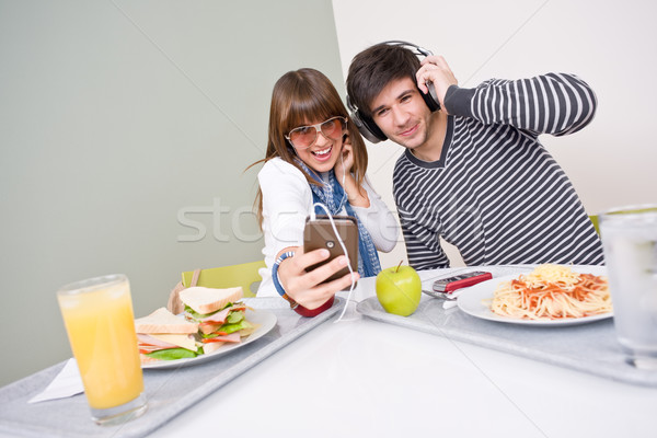 Student cafeteria - teenage couple having fun with music Stock photo © CandyboxPhoto