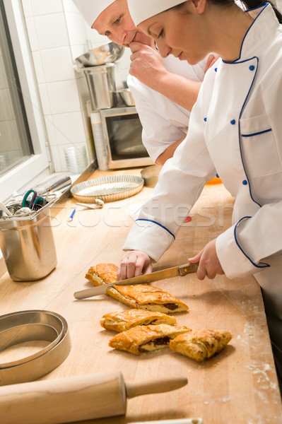 Female baker slicing strudel with male cook Stock photo © CandyboxPhoto