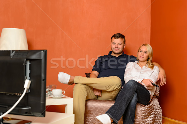 Young couple watching tv cuddling sitting armchair Stock photo © CandyboxPhoto