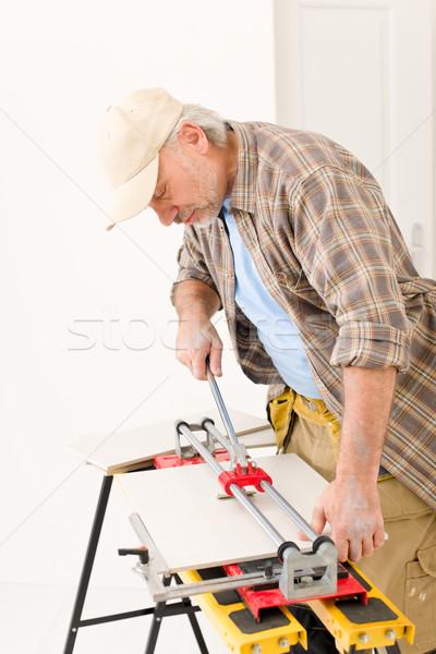 Stock photo: Home improvement - handyman cut tile