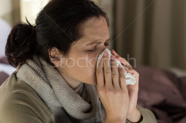 Ill woman sneezing in a tissue Stock photo © CandyboxPhoto