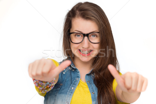 Stock photo: Girl in braces showing thumbs up isolated