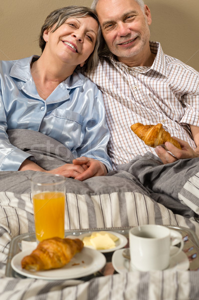 Happy retired couple eating croissant breakfast Stock photo © CandyboxPhoto