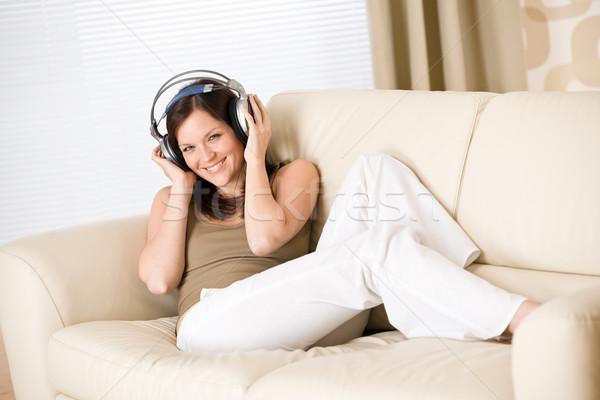 Foto stock: Feliz · mulher · fones · de · ouvido · sofá · salão