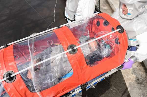 Biohazard team with virus patient in stretcher Stock photo © CandyboxPhoto