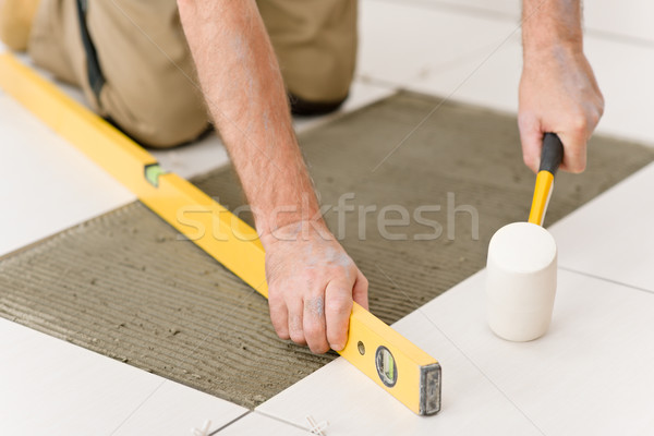 Stock photo: Home improvement, renovation - handyman laying tile