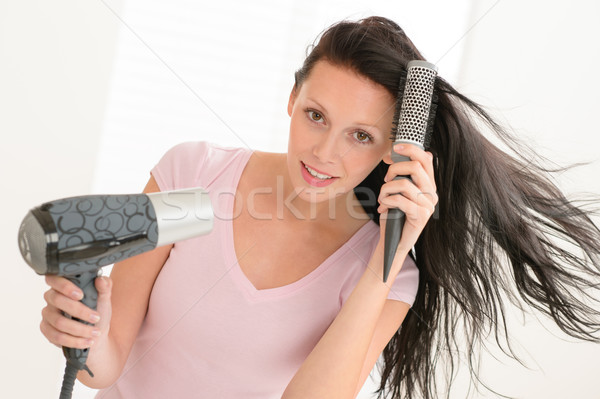 Woman blow-drying hair using round hairbrush Stock photo © CandyboxPhoto