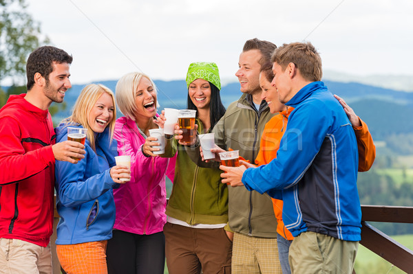 Happy friends clinking glasses drinking beer outdoors Stock photo © CandyboxPhoto
