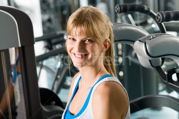 Smiling woman at fitness center exercise machine Stock photo © CandyboxPhoto