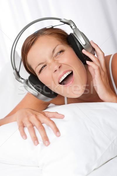 Młoda kobieta biały słuchawki słuchanie muzyki sypialni kobieta Zdjęcia stock © CandyboxPhoto