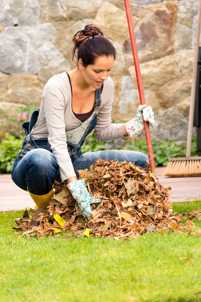 Stock photo: Young woman raking dry leaves pile backyard
