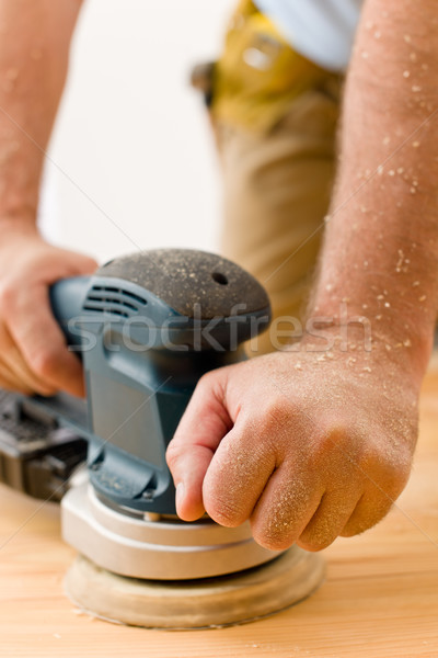 Stock photo: Home improvement - handyman sanding wooden floor