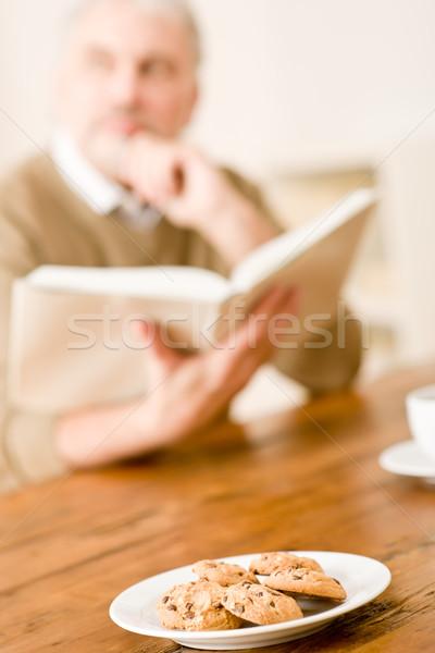 Senior homem maduro bolinhos mesa de madeira leitura livro Foto stock © CandyboxPhoto