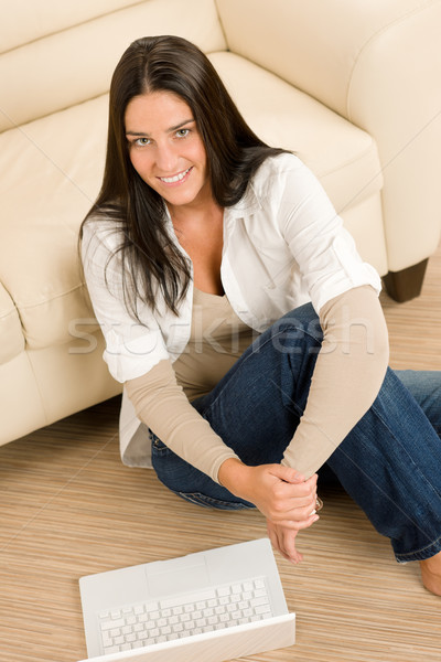 Woman with laptop sitting by couch smiling Stock photo © CandyboxPhoto
