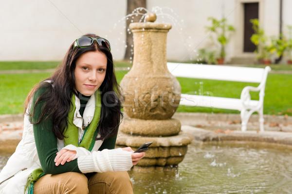 Stock fotó: ősz · park · szökőkút · fiatal · nő · tart · telefon