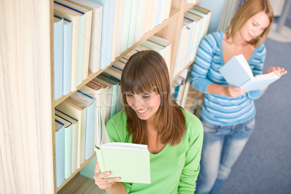 Stock photo: Student in library - two happy woman read book