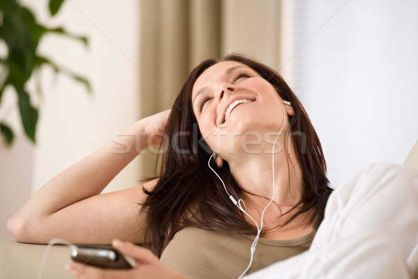 Woman holding music player listening in lounge Stock photo © CandyboxPhoto