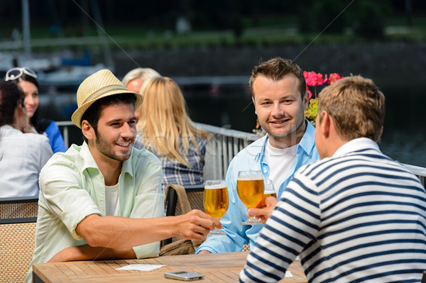 Three male friends drinking beer outdoor terrace Stock photo © CandyboxPhoto