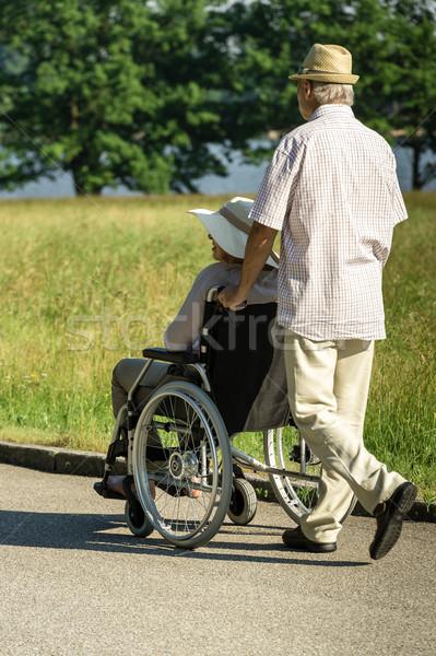 Senior husband pushing wife's wheelchair Stock photo © CandyboxPhoto