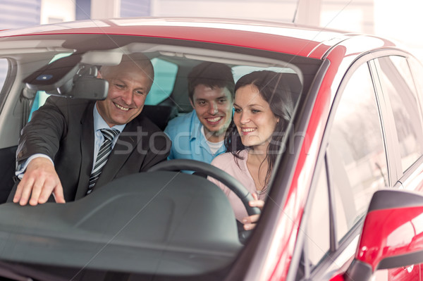 Stock photo: Cheerful couple looking around in new car