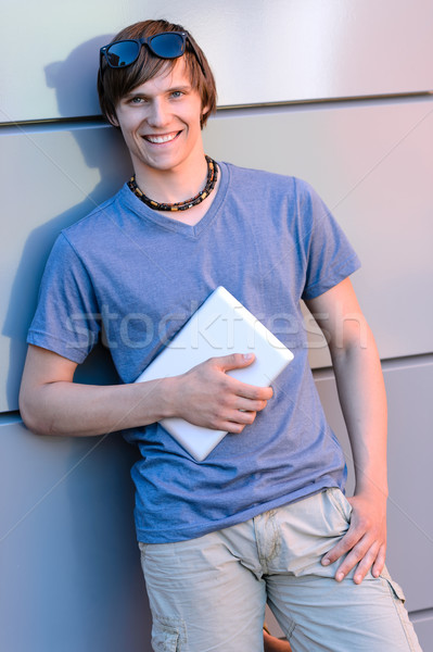 Smiling student boy leaning against modern wall Stock photo © CandyboxPhoto