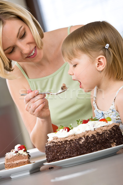 Stock photo: Mother and child tasting chocolate cake in kitchen