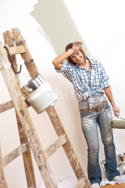Stock photo: Home improvement: Cheerful woman with paint roller