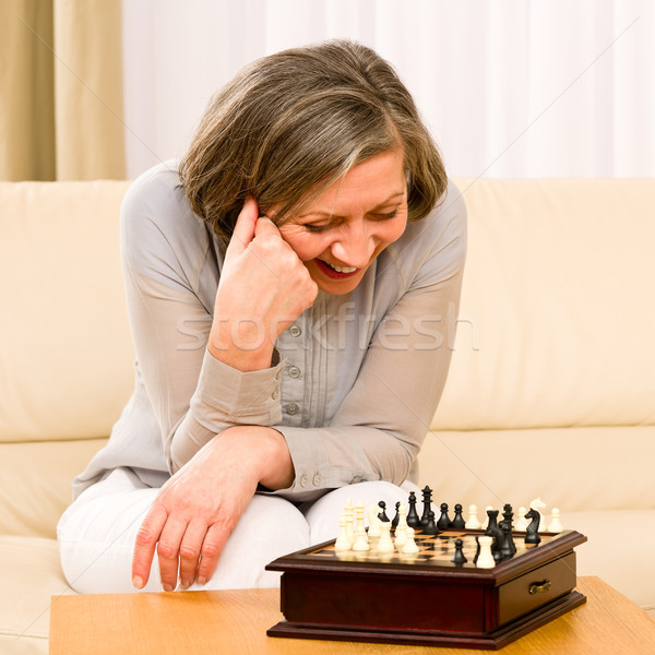 Stock photo: Senior woman play chess happy sit on sofa