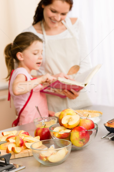 Foto d'archivio: Madre · figlia · guardare · cottura · ricettario · torta · di · mele