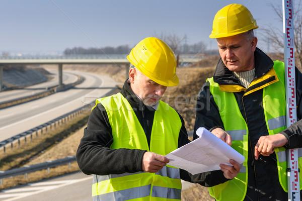 Stock photo: Geodesist read plans on construction site