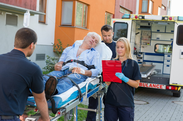 Emergency team assisting injured man on stretcher Stock photo © CandyboxPhoto